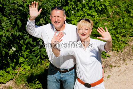 happy mature couple beckons