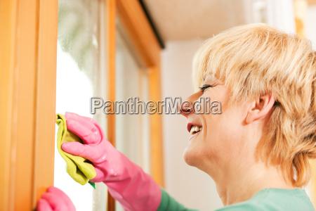 hausfrau putzt die fenster