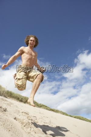 junger mann laeuft hinunter sandduene am