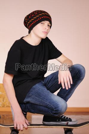 der teenager mit einem skateboard