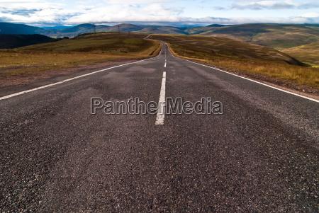 asphaltstrasse fuehrt in die weite v2