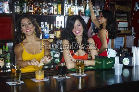 drei sexy junge kellnerinnen servieren getraenke