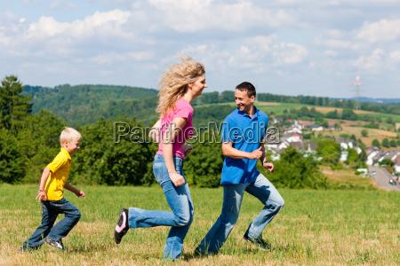 familie spielt fangen auf der wiese
