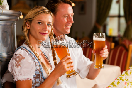 couple in traditional clothes drinking wheat