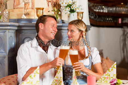 couple in traditional costume drinking white