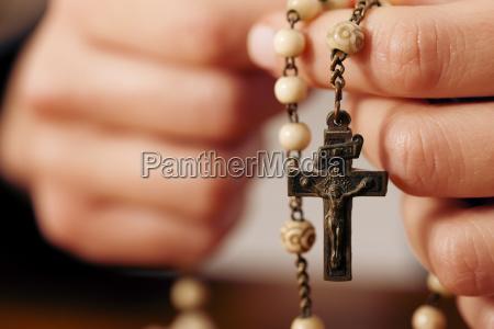 eine frau betet mit rosenkranz zu