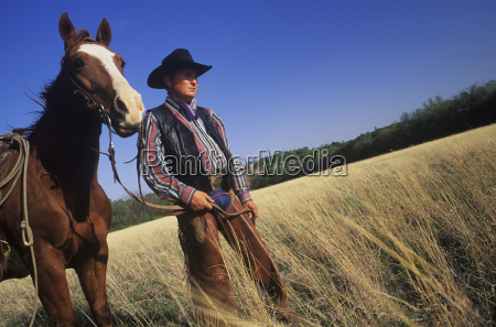 cowboy standing with a horse on