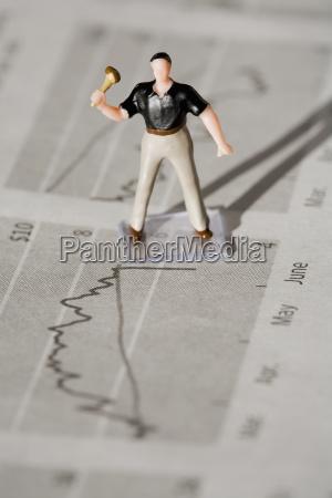 figur eines arbeiter auf einer finanzzeitung