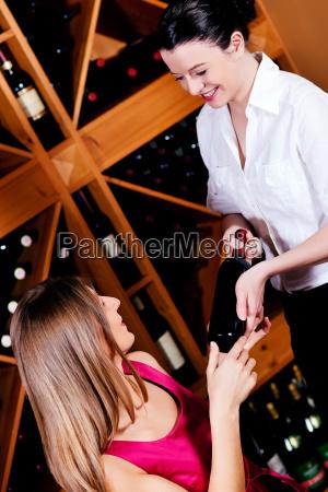 waitress at the restaurant serves wine