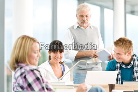 gymnasium drei schueler mit reifem professor