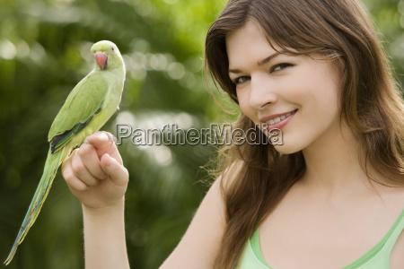 papagei auf der hand einer jungen