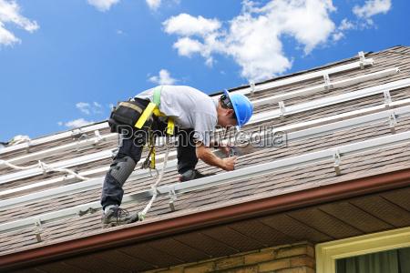 mann arbeitet auf dach installiert schienen
