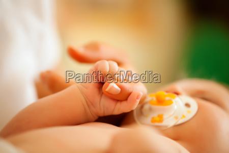 baby mit mutter greift nach hand