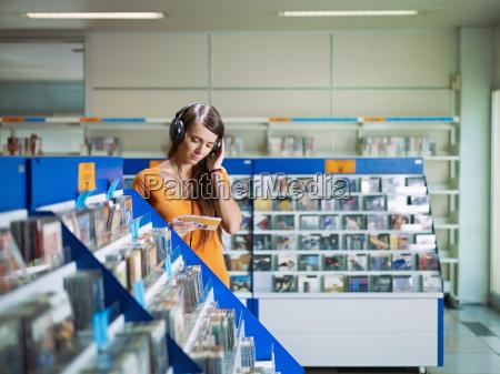 maedchen hoert musik im cd shop