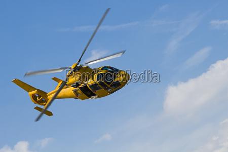 gelber hubschrauberflug im bewoelkten himmel