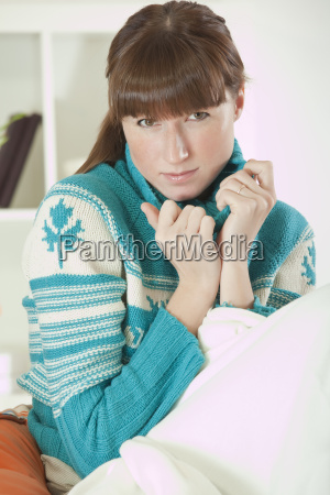 sad woman in sweater at home