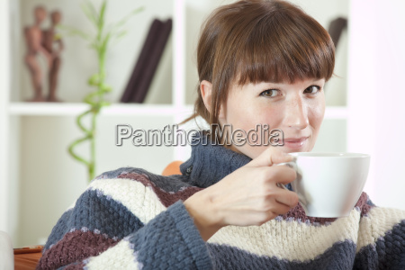 woman with cup tea on sofa