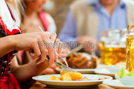 leute essen schweinebraten in restaurant