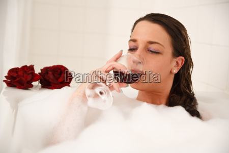 woman drinking wine in the bath
