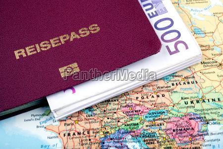 reisepass mit banknoten auf reisekarte