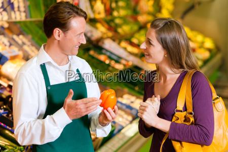 frau im supermarkt und verkaeufer