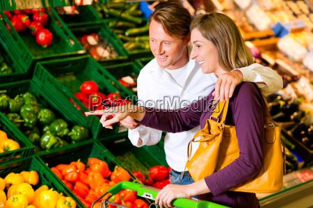 paar im supermarkt kauft gemuese
