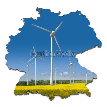windkraftraeder in einem rapsfeld in abstrakter