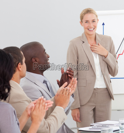 blond businesswoman standing smiling after a