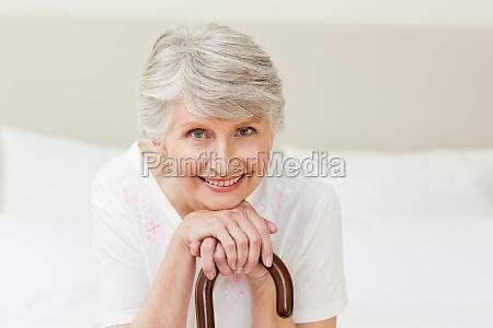 pensionierte frau mit ihrem gehstock zu