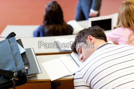schlafender maennlicher student waehrend einer universitaetslektion