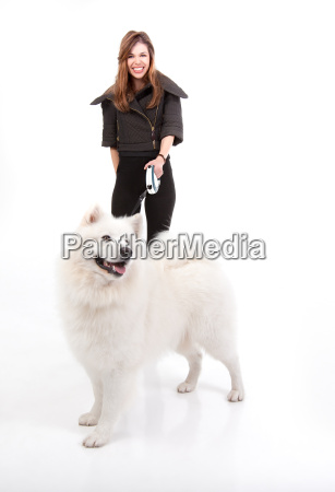 young woman walking a white dog
