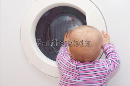 kleinkind vor waschmaschine