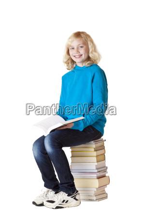 schulmaedchen sitzt auf schulbuechern und liest