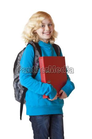 glueckliches schulmaedchen mit rucksack und ordner