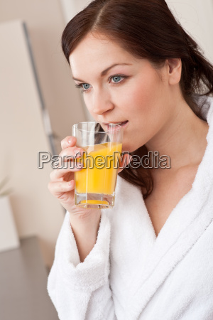 young woman drink orange juice in