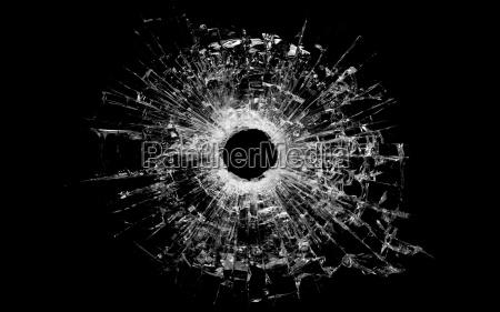 einschussloch in glas isoliert auf schwarz