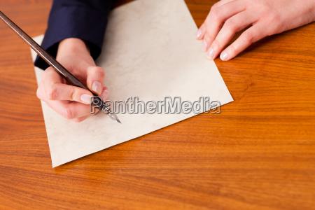 frau schreibt einen brief mit feder