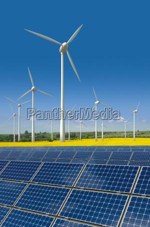 windkraftraeder und solarmodule in einem rapsfeld