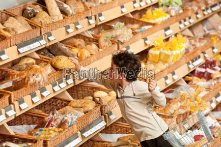 lebensmittelgeschaeft einkaufen kleiner junge kauft brot
