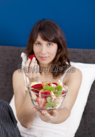 girl on bed eating fruits