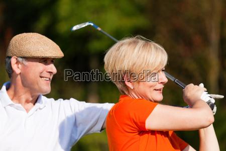 aelteres paar beim golfen