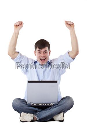 junger gluecklicher mann mit computer freut