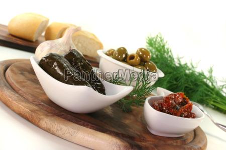 oliven gefuellte weinblaetter und eingelegte tomaten