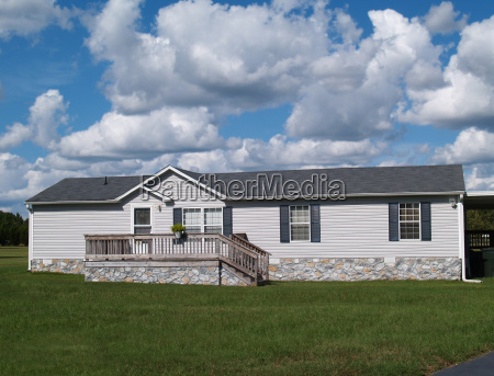 gray trailer home with stone foundation