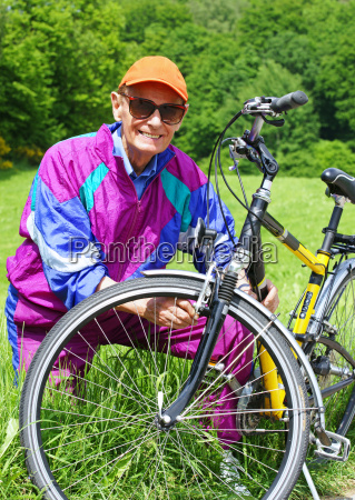 senior with bicycle in nature