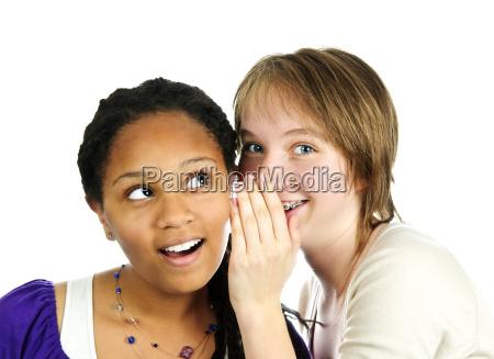 two girlfriends whispering