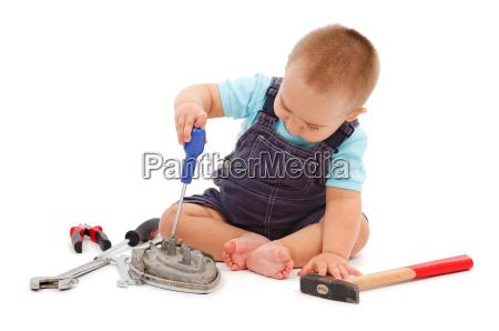 kleiner junge spielt mit werkzeugen