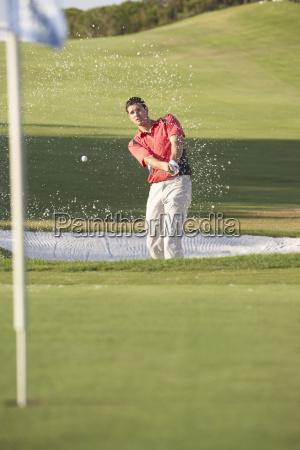 maennlicher golfspieler spielen bunkerschlag auf golfplatz