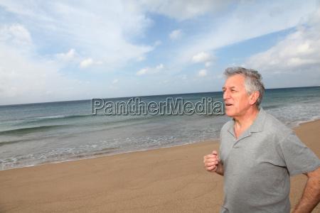 aelterer mann der auf den strand