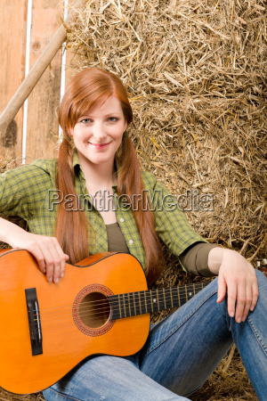 young country woman sitting on hay